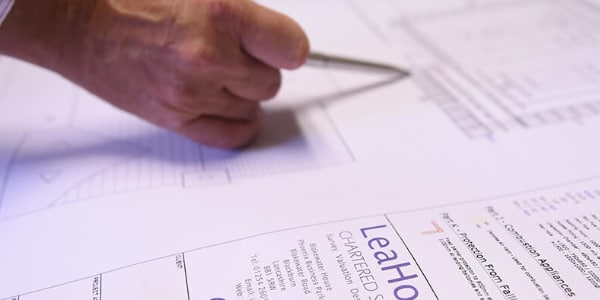 what do chartered surveyors do, this picture shows a chartered surveyor working on a survey.